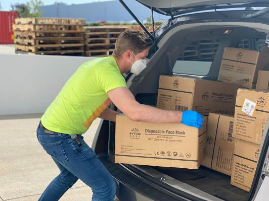 man loading boxes in boot of a car