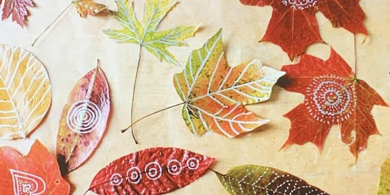autumn leaves in red, orange, green and yellow on light brown background
