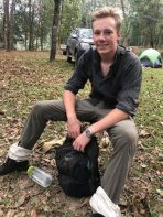 Young conservationist smiling sitting outdoors with backpack