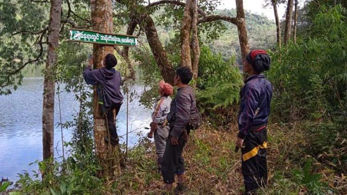 Posting no-littering sign at Naung Sai Lake, Myanmar