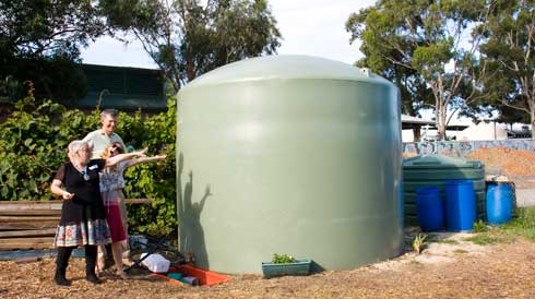 Randwick's proud community gardeners show their shiny, new rainater tank. Water is sourced from the stables adjacent to the garden.