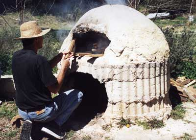 A cobb oven at Katoomba Community Garden, NSW. The cook is feeding in fuelwood to heat the oven. Once heated and the fire subsided, food is placed in for cooking.
