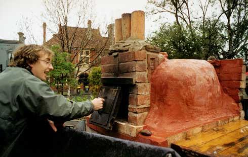 Victorian community garden network catclyst, Ben Neil, opens the door of a small cobb oven at an inner-urban community garden.