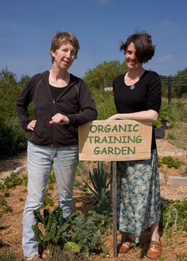 South Australian community gardn network coordinator, claire nettle (right), leans on a convenient sign with Fiona Campbell, Randwick City Council Sustainability Education Officer. Fiona uses the training garden for Council's Sustainable Gardening courses.