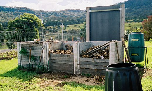A series of open compost bays with removable front sections made of boards.