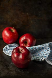 three red apples on brown surface