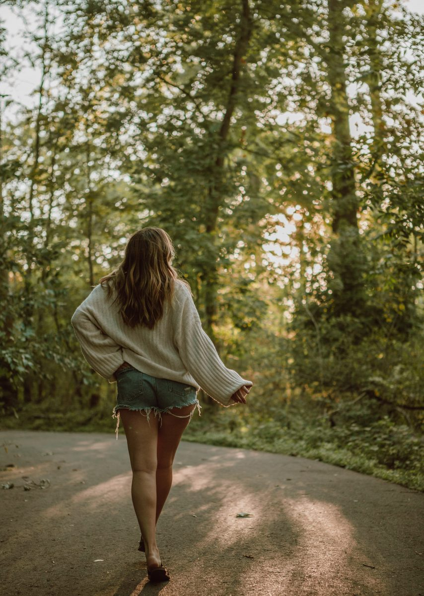woman in gray long sleeve shirt and blue denim shorts walking on pathway between trees during
