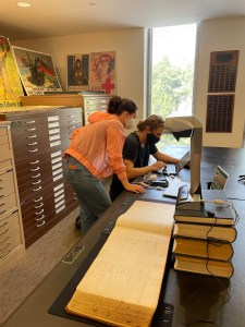 Color photograph of Emma Stout and Nate Nihart at the State Archives of NC. They are looking at an image on a laptop. A large ledger book is on the table next to them.