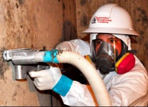 A state-certified mold remediation specialist applies dry ice to disinfect wooden beams of mold.