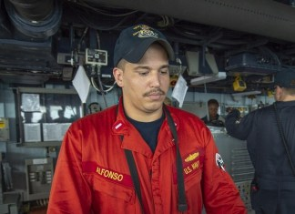 Naval officer stands watch on guided missile destroyer