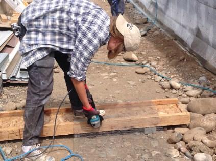 Intern Beatrice cuts metal lathe using a grinding wheel
