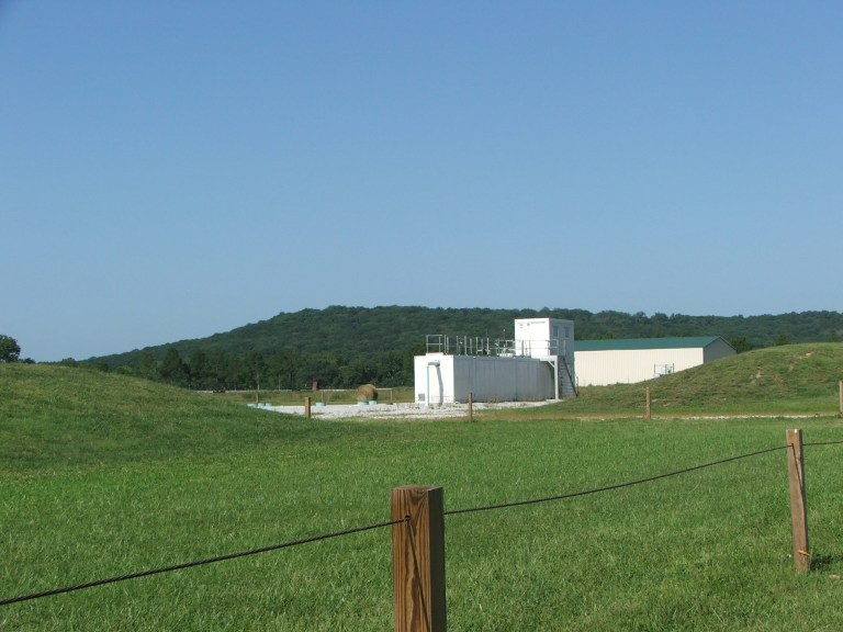 Wastewater treatment plant in the distance with pasture in the foreground.