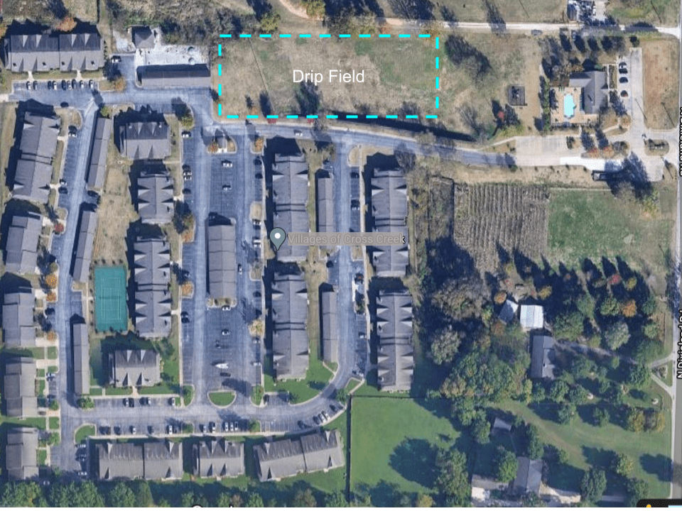 Satellite view of an apartment complex with wastewater drip field outlined.