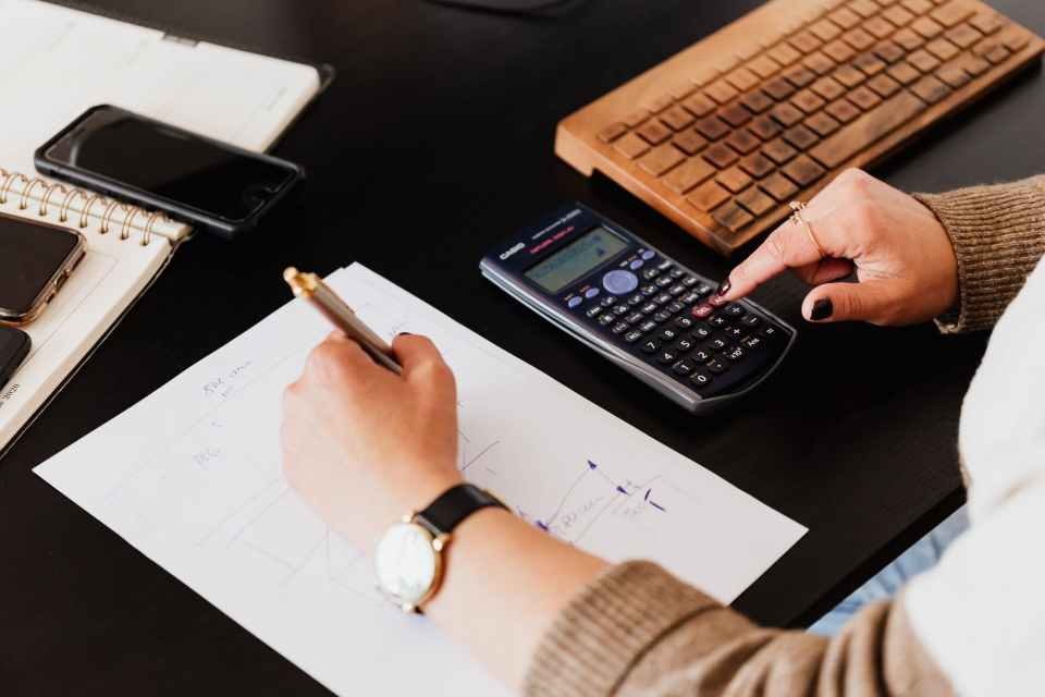 crop woman using calculator and taking notes on paper