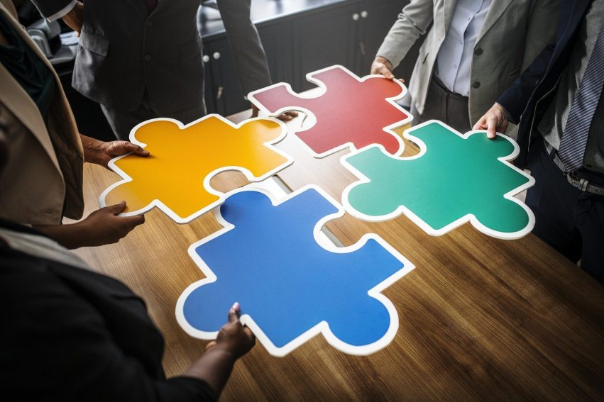 Business people with jigsaw pieces