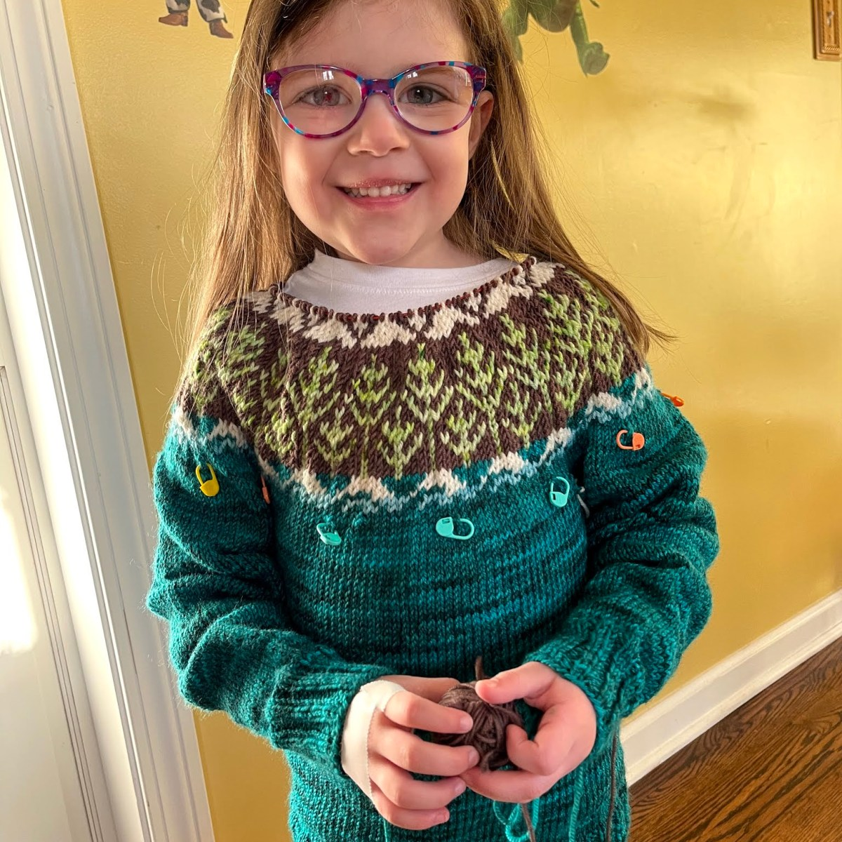 a little girl models a hand knitted sweater in progress