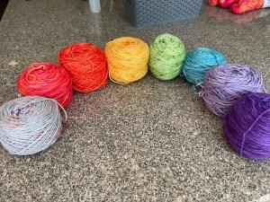 A semicircle of wound yarn in rainbow order: grey speckled, pinkish orange, orange, yellow, green, blue, light purple and dark purple