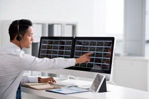 Trader przed monitorami, na których znajdują sięwykresy