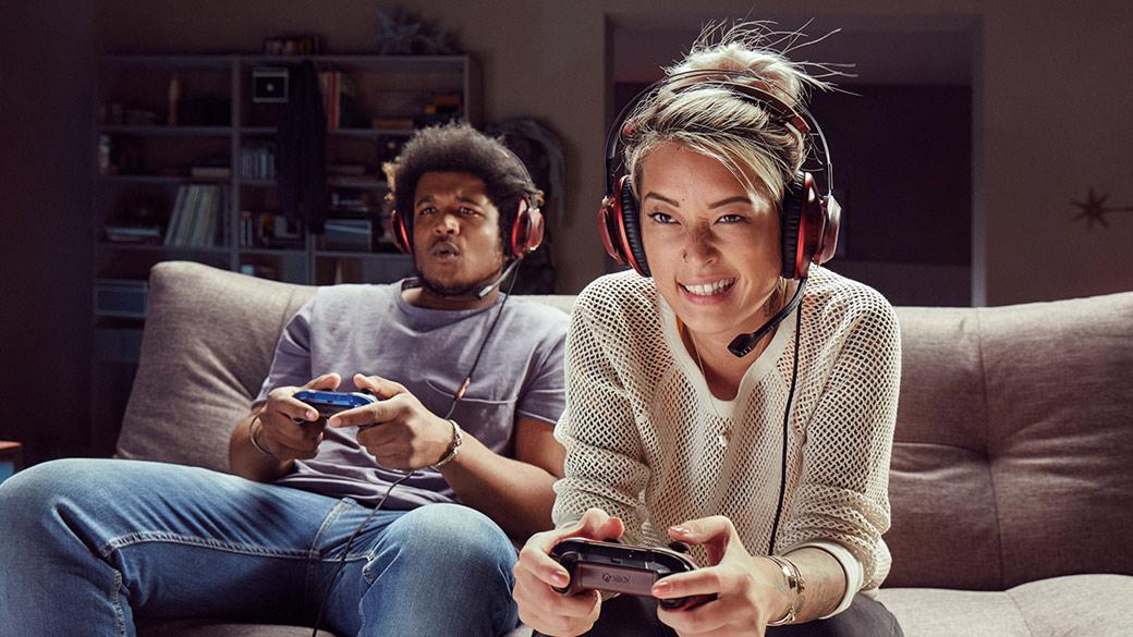 Un hombre y una mujer sostienen controles Xbox, jugando a videojuegos