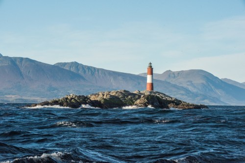 A lighthouse in the Beagle Channel surrounded by dark seas and mountains
