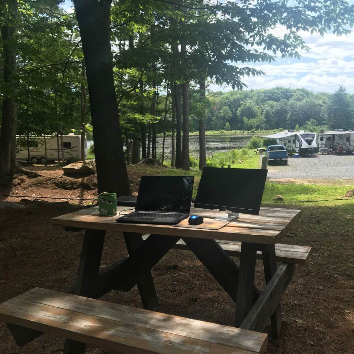 laptop and monitor on picnic table at campsite
