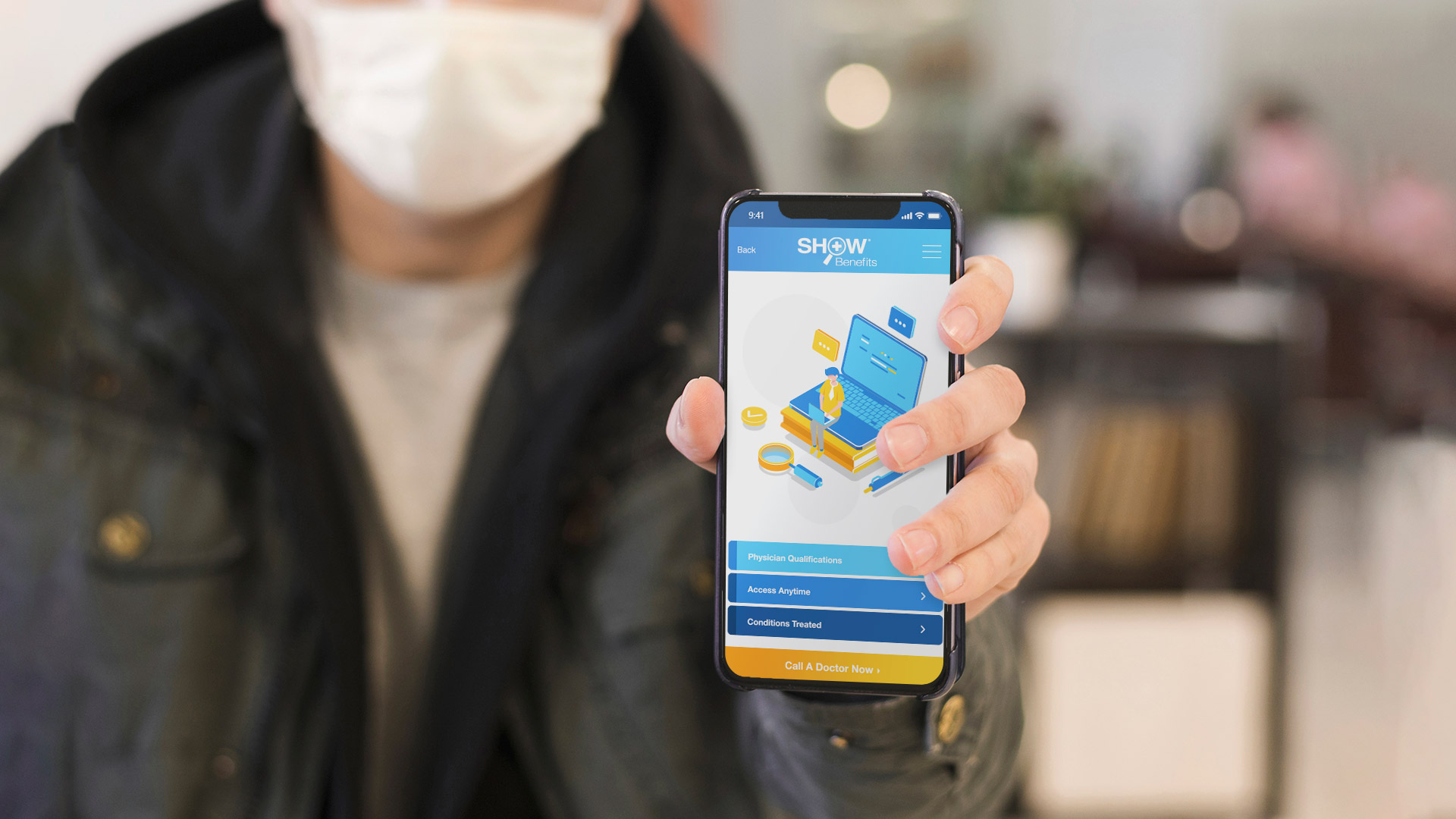 Man with medical face mask holds up his smartphone with the SHOWBenefits App open on the 24/7 Doctor Screen