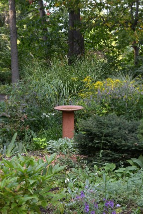 Birdbath anchors the herb beds