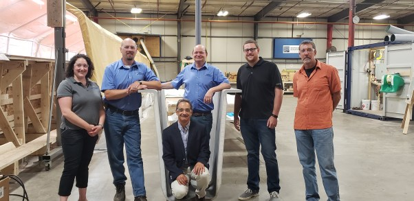 Habib Dagher (center front) and Bill Davids (right) from the University of Maine and (L-R) Carmala Buzzell, Wendell Harriman, Ken Sweeney, and Tim Kenerson from AIT Bridges with a CT Girder developed in the UMaine Composites Center.