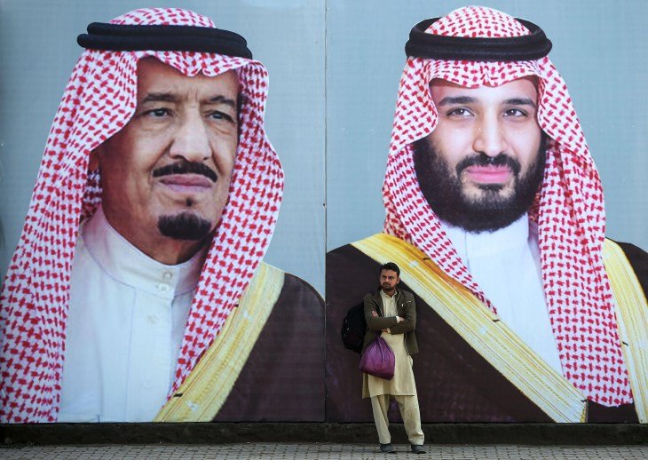 A man stands in front of billboards showing portraits of Saudi Arabian Crown Prince Mohammed bin Salman and his father and Saudi Arabia's King Salman bin Abdulaziz displayed on a street ahead of the prince's arrival in Islamabad on February 15, 2019.