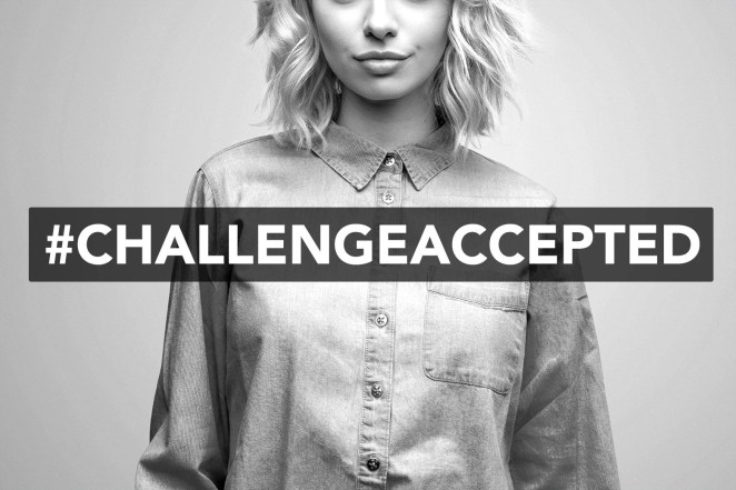 A woman posing with a #ChallengeAccepted hashtag.
