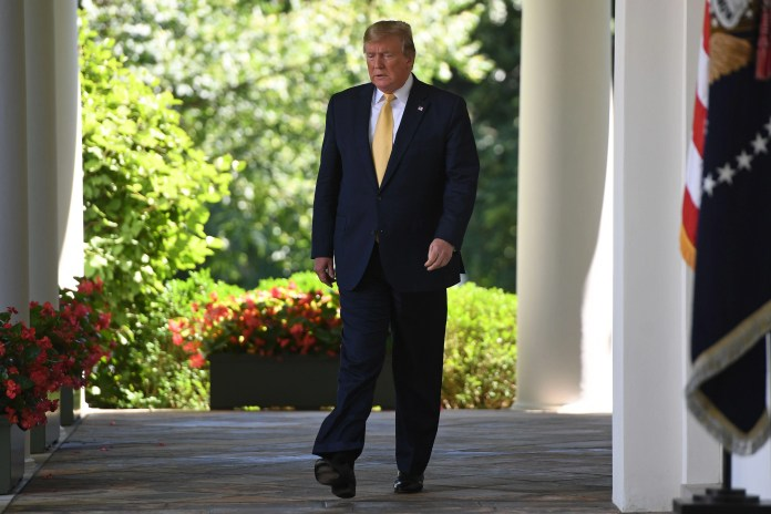 President Donald Trump walks to the Rose Garden of the White House.
