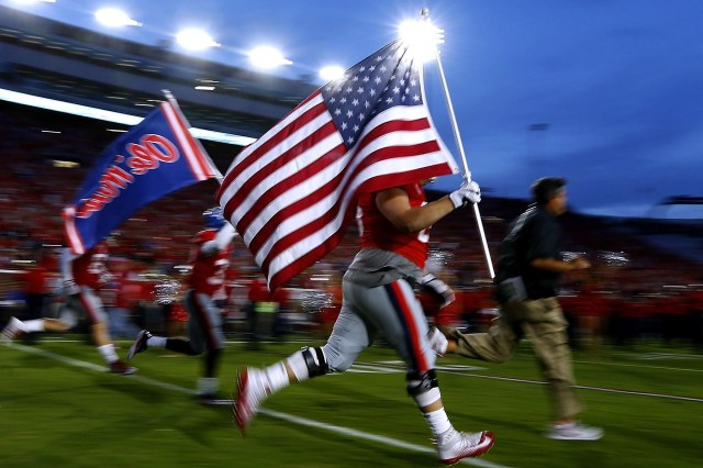 Ole Miss football players carry an American flag as they take the field before a game in Oxford, Mississippi.