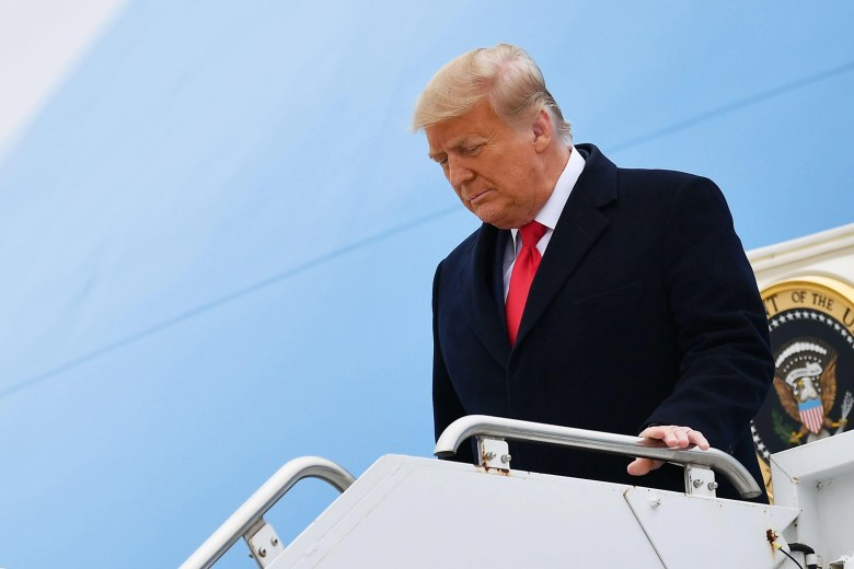 Trump steps off Air Force One with his head slightly bowed