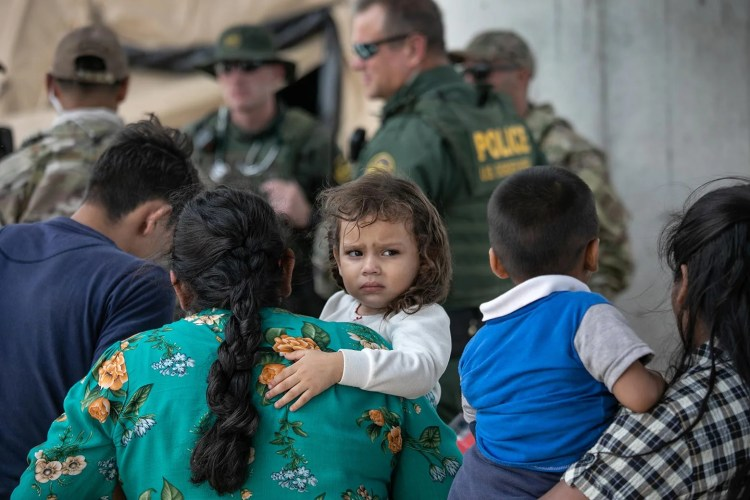 Immigrants waiting to be interviewed by U.S. Border Patrol agents after they were taken into custody in McAllen, Texas.
