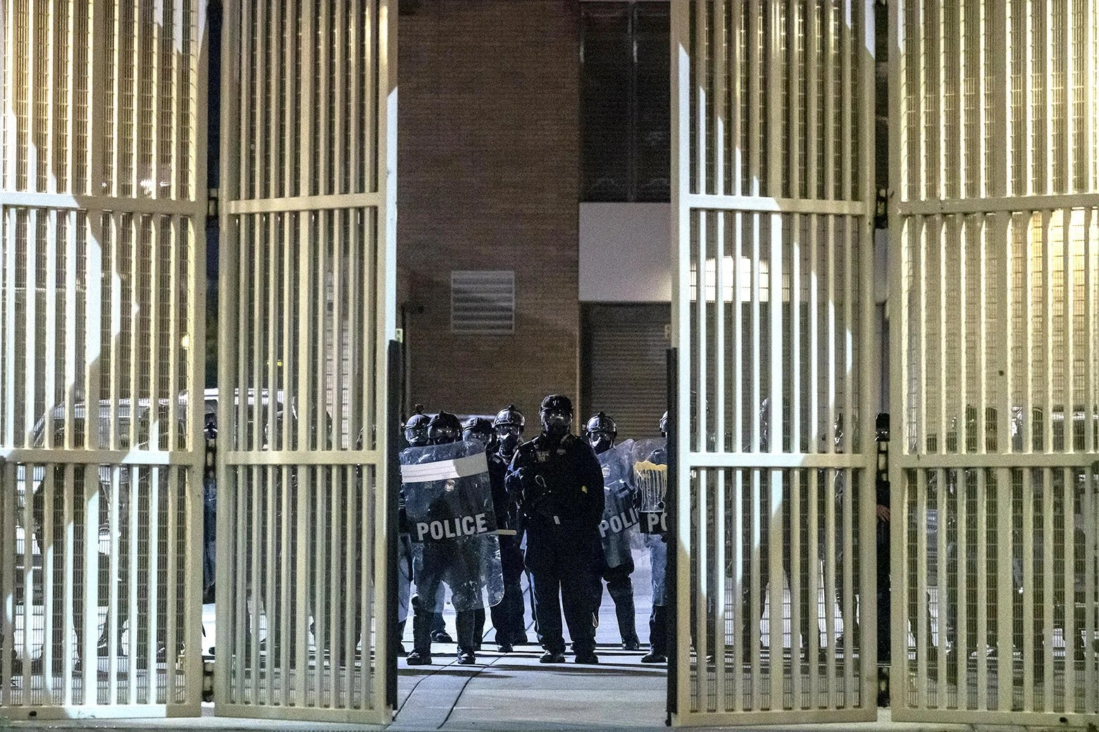Federal officers guard the front gate of the ICE detention center in Portland, Oregon, during a protest on Sept. 18.