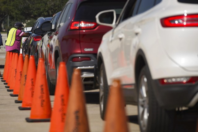 Orange cones along a line of cars with a poll worker standing next to the front car.