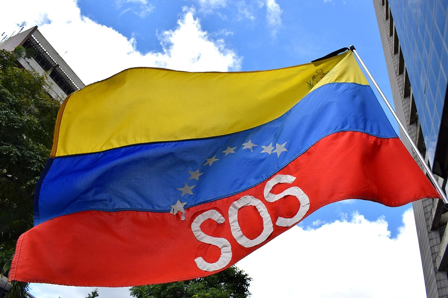 An SOS flag flies above protesters at a July 2019 march in Caracas.