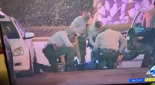 News footage shows law enforcement officers arresting reporter Josie Huang in Los Angeles, California on Sept. 12, 2020.
