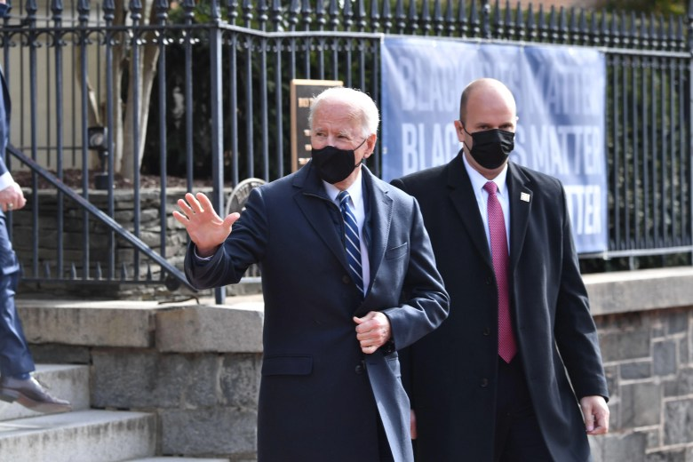 A masked Biden waves to crowds as he leaves church.