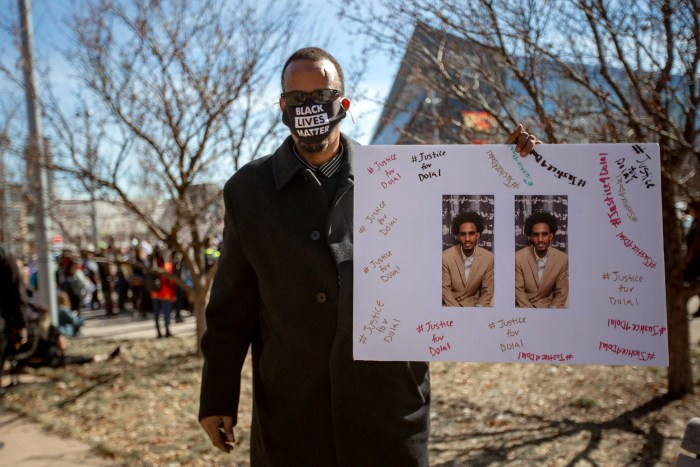 """A man wearing a Black Lives Matter mask holds up a poster with photos of Dolal Idd surrounded by the words """"Justice for Dolal"""""""