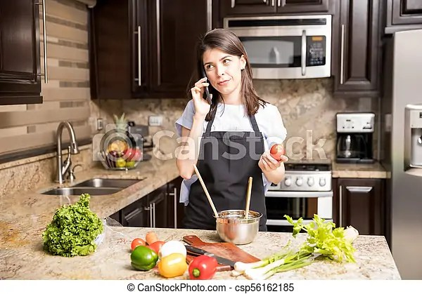 kitchen phone roman shades woman using while cooking in portrait of beautiful csp56162185