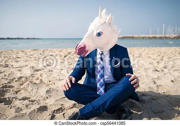 Young Trendy Man In Funny Mask And Elegant Suit On Vacation Unicorn Sits On The Beach On Background Of Sea And Sky