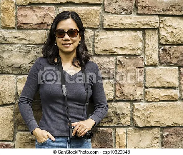 Asian Women Holding Camera Against Stone Wall Csp10329348