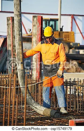 Builder worker at concrete pouring work. Builder worker standing near trailer-mounted boom concrete pump on metal rods reinforcement of concrete ...