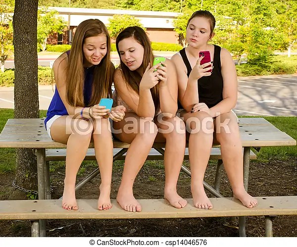 Picture of Pre-teen girls texting while hanging out in front of their... csp14046576 - Search Stock Photography, Photos, Images, and Photo Clipart