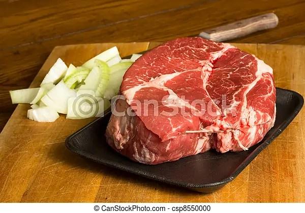 Chuck roast. Raw cut of beef chuck roast and onions on a cutting board.