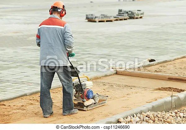 Concrete worker work with compactor. Builder worker at sand ground compaction with vibration plate compactor machine before