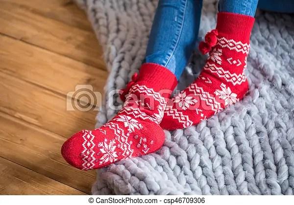 Female feet in socks. Female feet in cute red and white socks on knitted blanket.