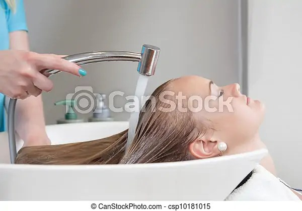 Hair rinse in beauty salon. Young female soman having her hair washed and rinsed in beauty salon.