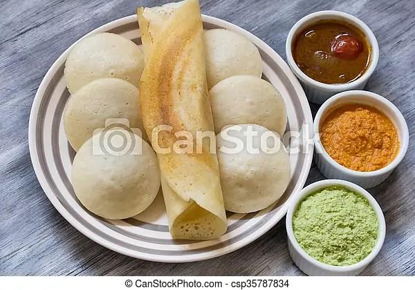 Indian food idli and dosa with chutney and sambar.